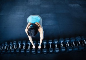 Woman takes a dumbbell at gym